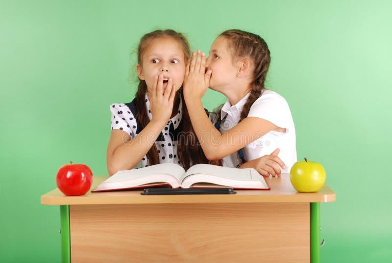 Zwei Schulmädchen, welches die Geheimnisse sitzen an einem Schreibtisch vom Buch teilt lizenzfreie stockfotografie