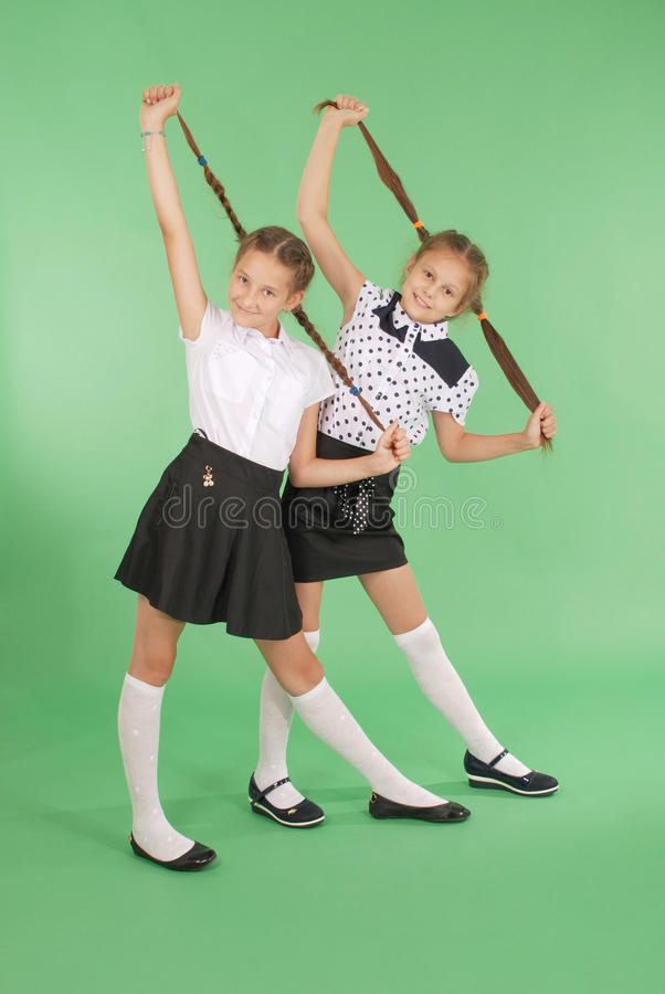 Zwei Schulmädchenspiele mit dem geflochtenen Haar stockfotografie