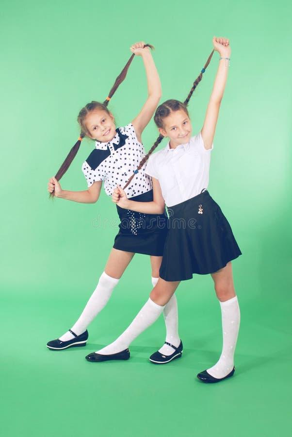 Zwei Schulmädchenspiele mit dem geflochtenen Haar lizenzfreie stockfotografie