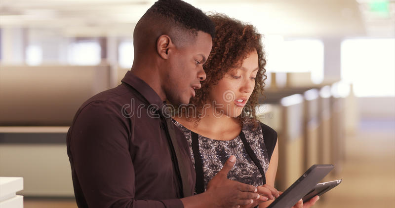 Zwei schwarze Büroangestellte, die Auflagen an einem modernen Arbeitsplatz verwenden stockfoto