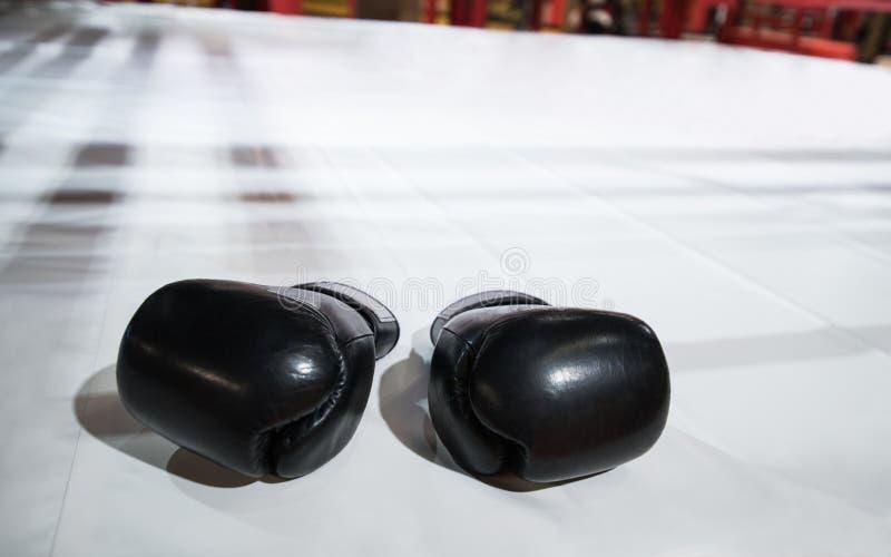 Zwei schwarze Boxhandschuhe liegen auf dem Boxring im Weiß Das sha stockfotos