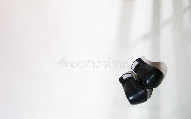 Zwei schwarze Boxhandschuhe liegen auf dem Boxring im Weiß Das sha lizenzfreie stockfotos