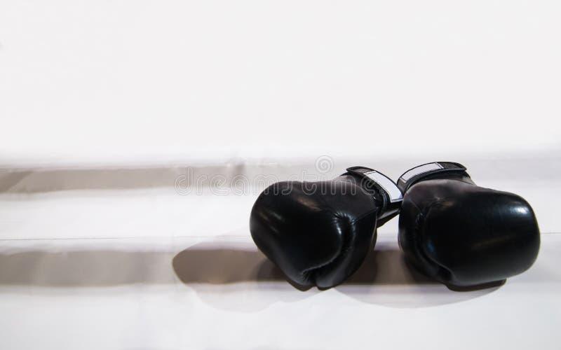 Zwei schwarze Boxhandschuhe liegen auf dem Boxring im Weiß Das sha lizenzfreies stockfoto