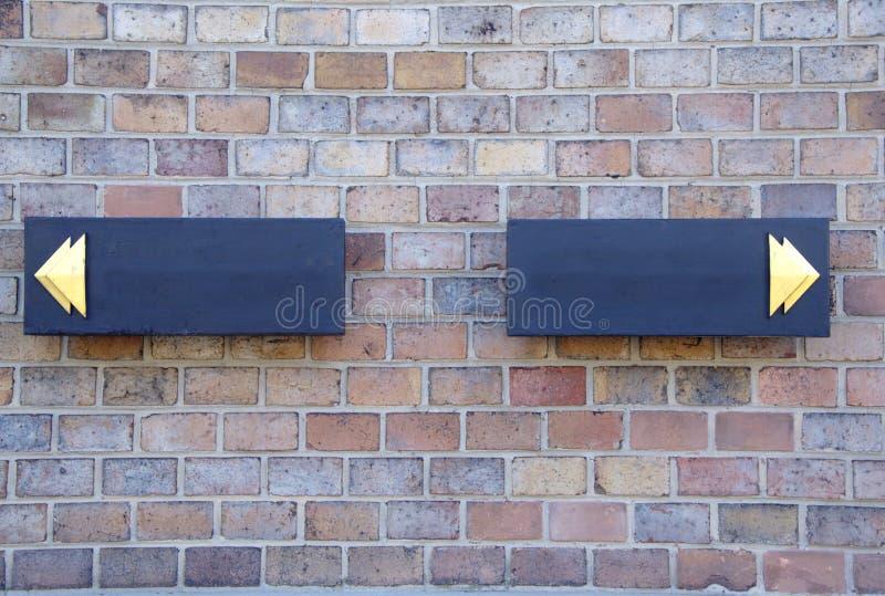 Zwei schwarze dirrectional Zeichen mit goldenen Pfeilen in den verschiedenen Richtungen stockfotografie