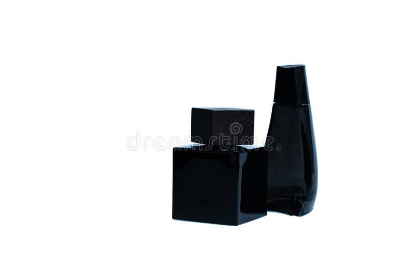 Zwei schwarze Flaschen Parfüm auf einem weißen Hintergrund lizenzfreie stockfotografie