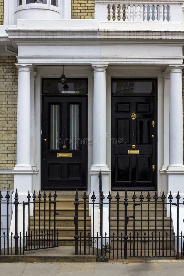 Zwei schwarze Holztüren zum Wohngebäude in London Typische T?r in der englischen Art lizenzfreies stockfoto