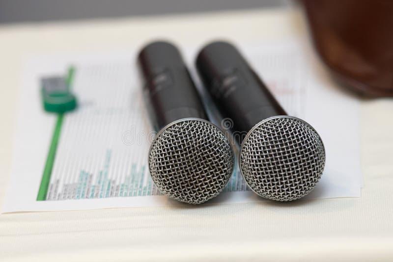 Zwei schwarze Karaokemikrophone stehen auf einer weißen Tabelle lizenzfreies stockbild