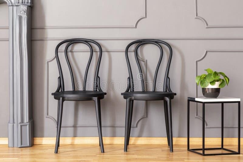 Zwei schwarze Stühle, die nahe bei Marmorbeistelltisch mit frischem pl stehen stockbild