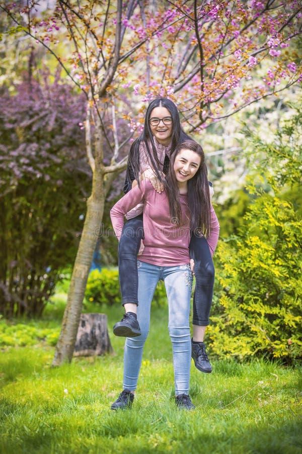 Zwei Schwesterfreunde, die Spaß im Park haben lizenzfreie stockbilder