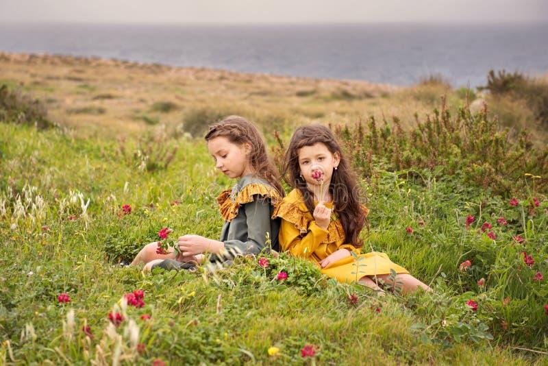 Zwei Schwestermädchen in altmodischer Weinlese kleidet die Schnüffelnblumen, die auf einer Hochebene nahe dem stürmischen Meer si lizenzfreies stockfoto