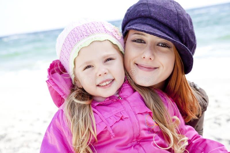 Zwei Schwestern 4 und 21 Jahre alt am Strand stockfotografie