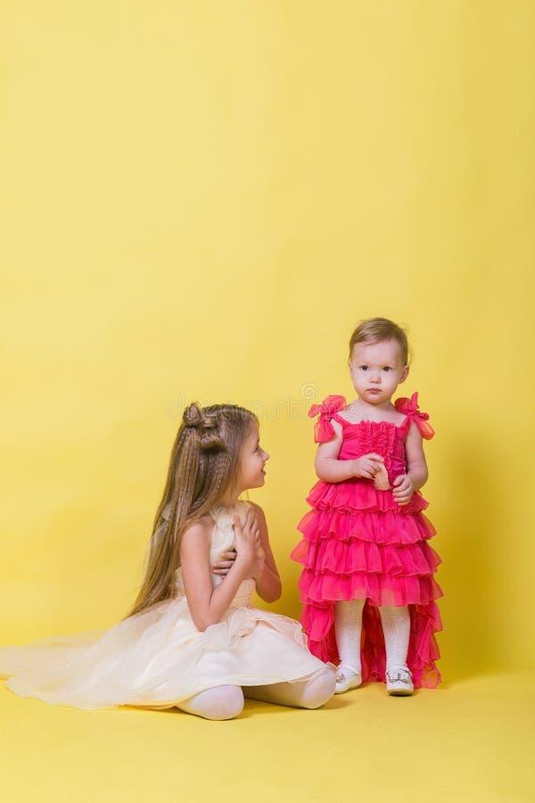 Zwei Schwestern in den Kleidern auf einem gelben Hintergrund im Studio stockfotografie