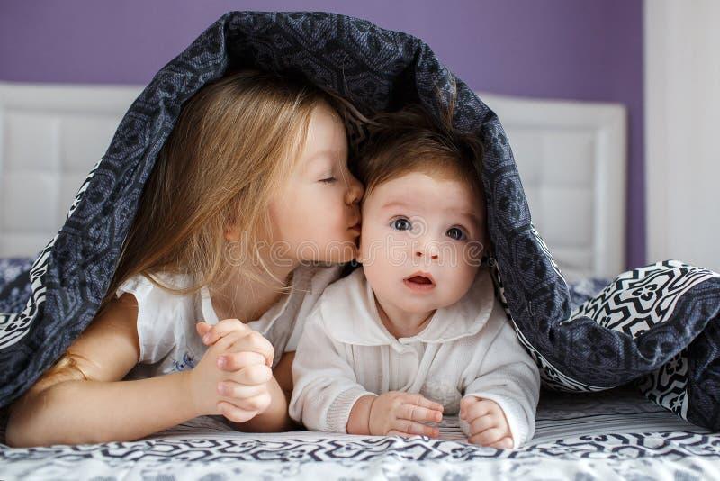 Zwei Schwestern, die auf dem Bett unter der Decke liegen lizenzfreie stockbilder