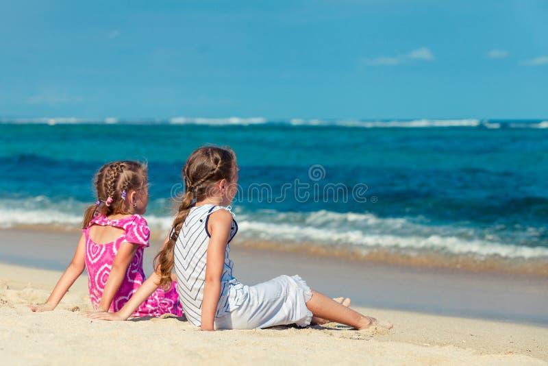Zwei Schwestern, die auf dem Strand und dem Blick in dem Ozean sitzen stockbilder