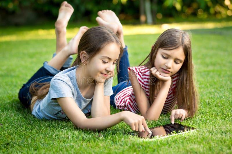 Zwei Schwestern, die draußen auf Gras liegen und auf digitaler Tabelle spielen lizenzfreie stockbilder