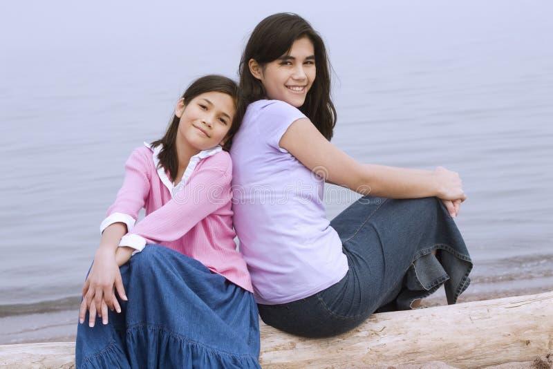 Zwei Schwestern, die durch Strand sitzen lizenzfreie stockfotos