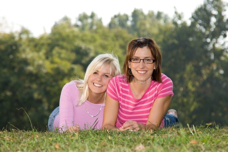 Zwei Schwestern, die im Gras liegen lizenzfreies stockbild