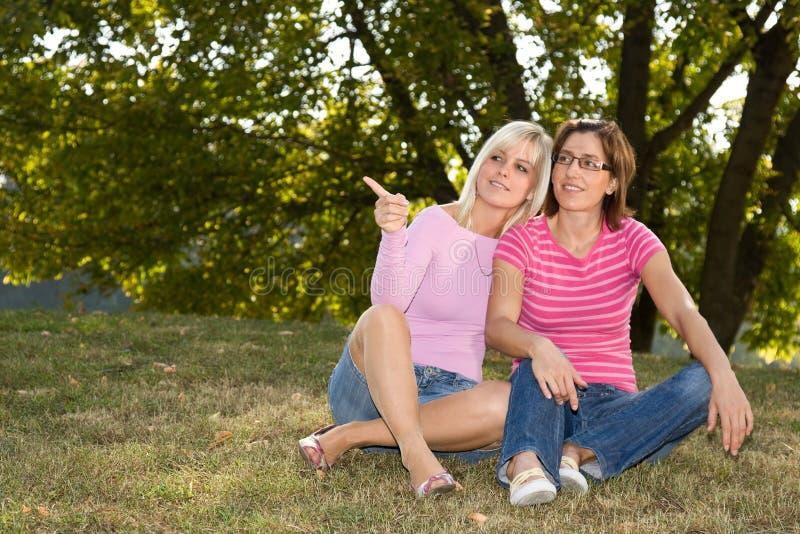 Zwei Schwestern, die im Gras sitzen lizenzfreies stockfoto