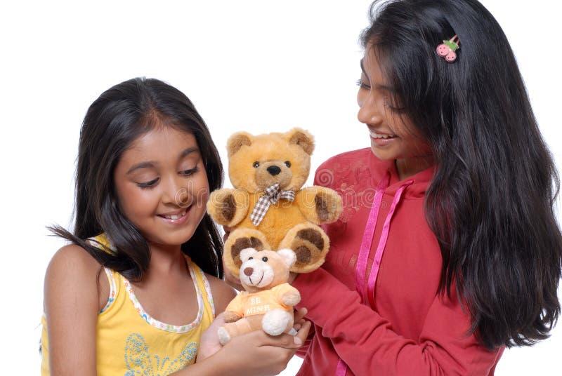 Zwei Schwestern, die mit Teddybären spielen stockfotos