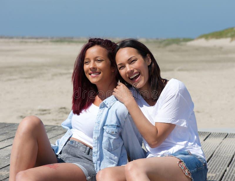 Zwei Schwestern, die am Strand lächeln lizenzfreies stockbild