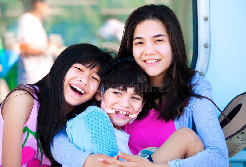 Zwei Schwestern, die um behindertem kleinem Bruder sich kümmern lizenzfreie stockfotos