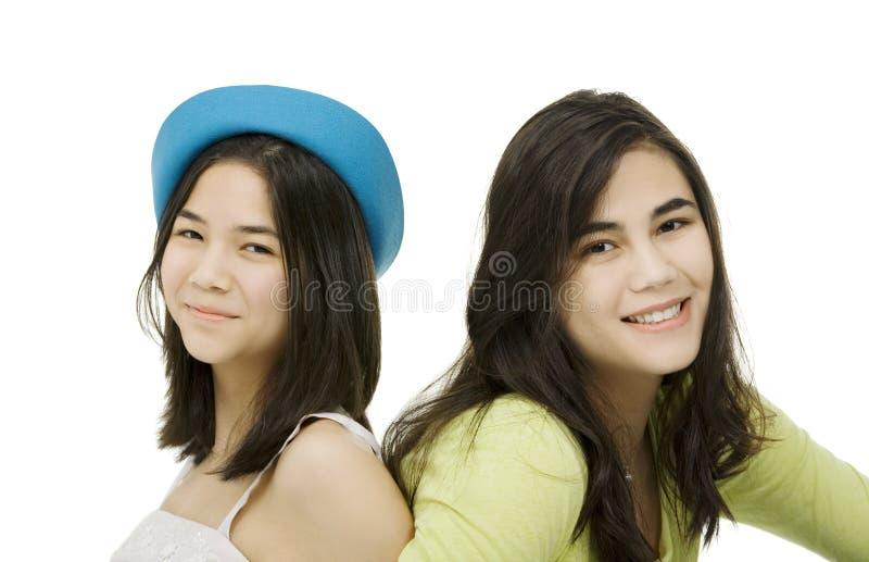 Zwei Schwestern, die zusammen, getrennt auf Weiß sitzen lizenzfreie stockfotos