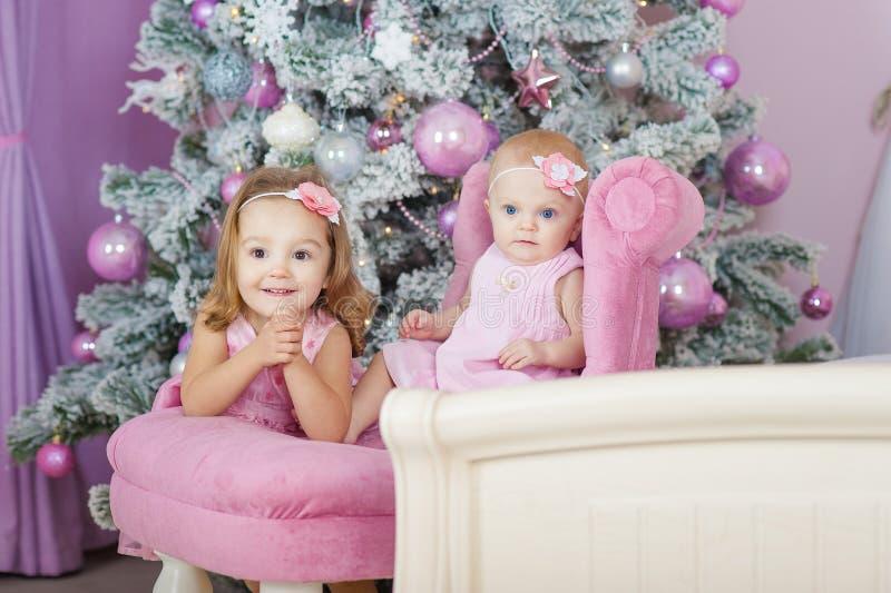 Zwei Schwestern zu Hause mit Weihnachtsbaum Porträt von glücklichen Kindermädchendekorationen stockbilder