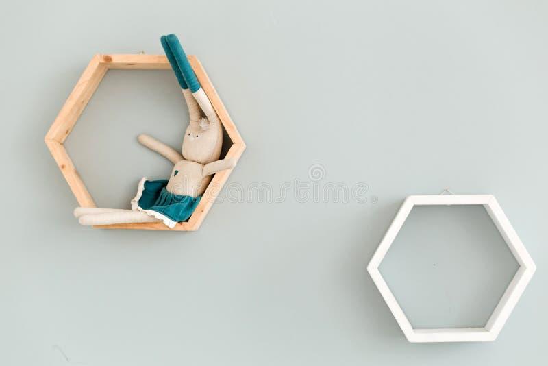 Zwei sechseckige Rahmen hängen an der blauen Wand und ein Spielzeughase sitzt auf einem von ihnen lizenzfreies stockbild