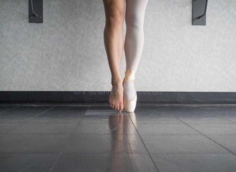 Zwei Seiten zu ein Ballerina ` s Füßen, beide in und aus ihren Tanzenballettschuhen stockfotografie