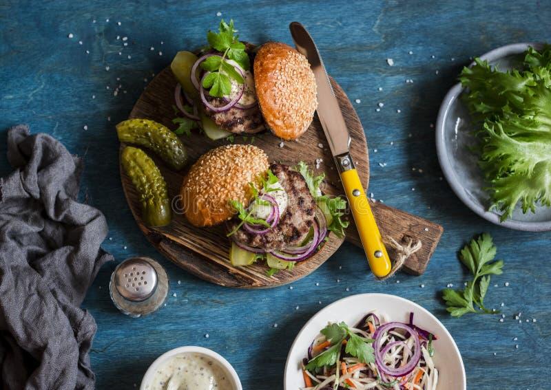 Zwei selbst gemachte Burger auf einem hölzernen Schneidebrett, Draufsicht lizenzfreie stockfotografie