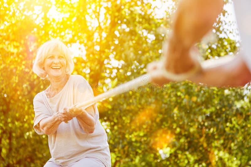Zwei Senioren, die Tauziehen im Sommer spielen stockfotos