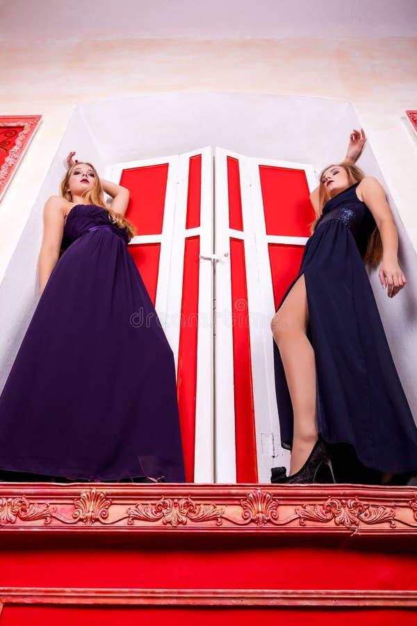 Zwei sexy Frauen auf Schwelle im reichen Weinleseinnenraum lizenzfreie stockfotografie