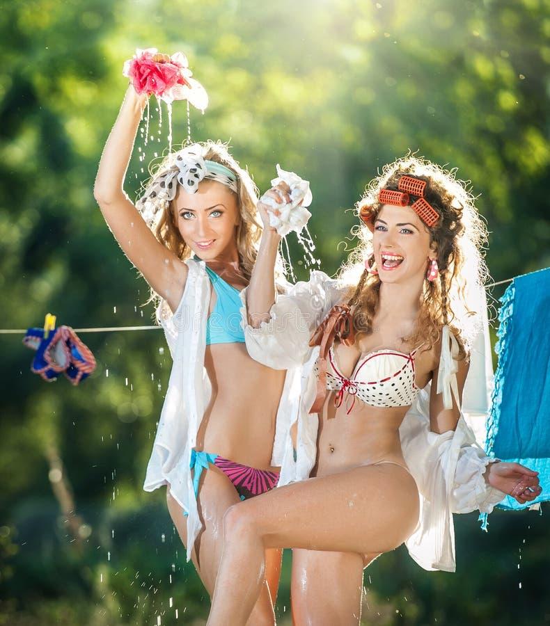 Zwei sexy Frauen mit den provozierenden Ausstattungen, die Kleidung setzen, um in der Sonne zu trocknen Sinnliche junge Frauen, d stockbild