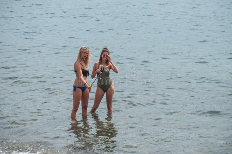 Zwei sexy Mädchen im Badeanzug, der ein selfie im Wasser mit Smartphone nimmt stockfotografie