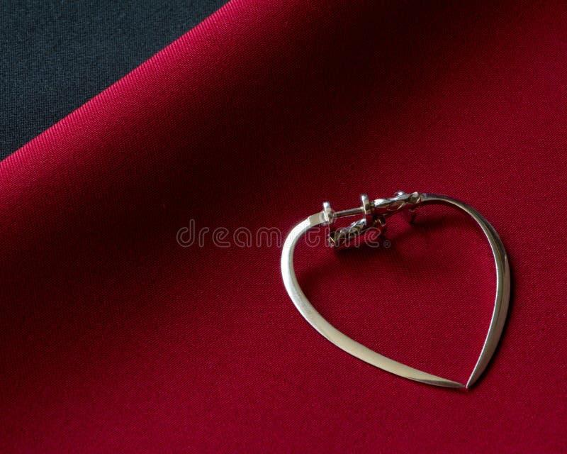 Zwei silberne Ohrringe in Form eines Herzens auf einer roten Oberfläche, das Konzept der Liebe lizenzfreie stockfotos
