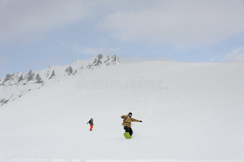 Zwei Snowboarder, die vom Gipfel des Berges gleiten lizenzfreie stockbilder