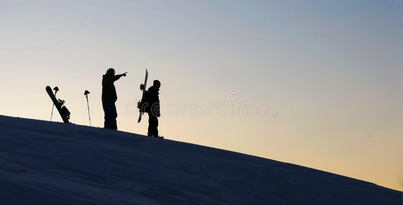 Zwei Snowboarders im Sonnenuntergang stockfotografie