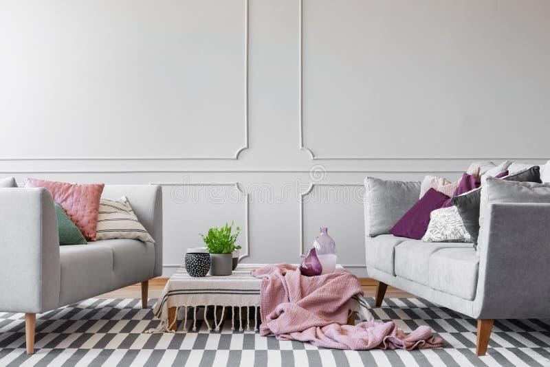 Zwei Sofas mit Los von Kissen und von Couchtisch mit Anlage im Topf, in den Glasvasen und in den Kaffeetassen im modernen Wohnzim stockfoto