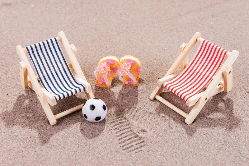 Zwei Sonnenruhesessel mit Ball und Schuhe auf dem Strand lizenzfreies stockfoto