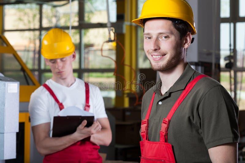 Zwei Spezialisten, die an der Fabrik arbeiten lizenzfreie stockbilder
