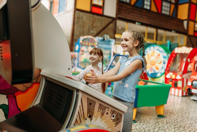 Zwei Spiele der kleinen Mädchen auf Videospielmaschine lizenzfreie stockfotos