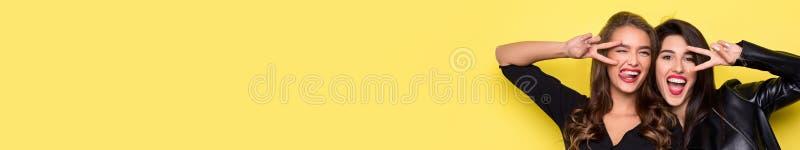 Zwei spielerische Mädchen, die Vzeichen nahe Augen auf Gelb gestikulieren vektor abbildung