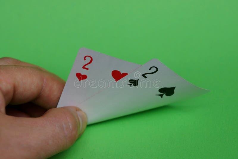 Zwei Spielkarten in den Fingern von Händen auf einem grünen Hintergrund lizenzfreies stockbild