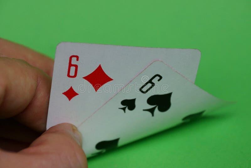 Zwei Spielkarten mit einem Paar sixes in den Fingern von Händen auf einer grünen Tabelle lizenzfreie stockfotografie
