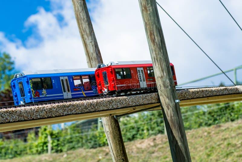 Zwei Spielzeuglokomotiven, ein blau und ein Rot, auf einer Holzbrücke lizenzfreie stockbilder