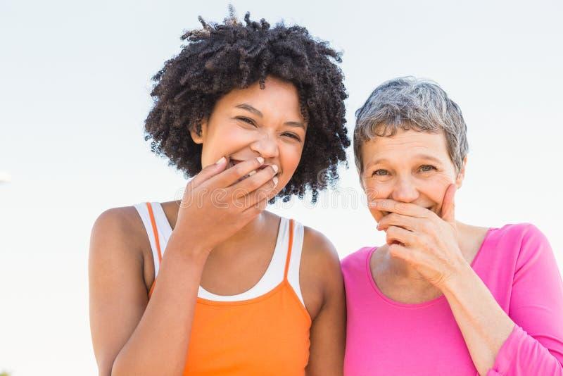Zwei sportliche Frauen, die zur Kamera lachen lizenzfreie stockfotografie