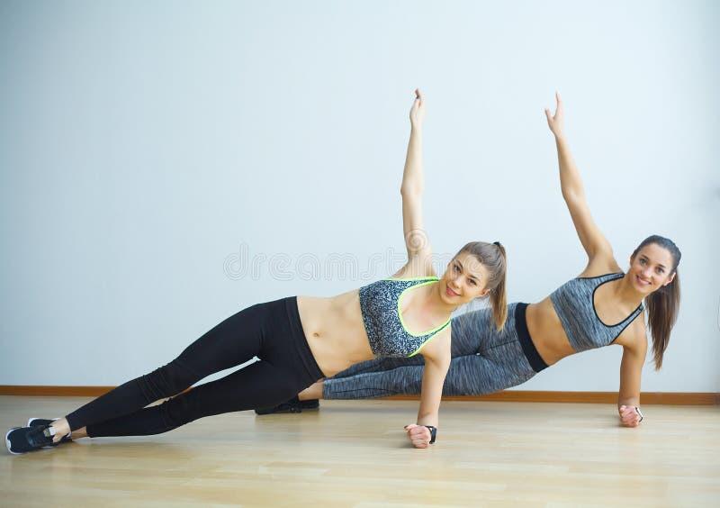 Zwei sportliche Mädchen, die Übungen tun, ups in Turnhalle lizenzfreie stockfotos