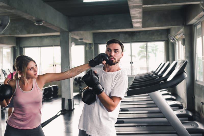 Zwei sportliche Paare bilden Verpacken im Fitness-Club, junge Frau ist der knockout aus, der zu ihrem Freund, zu Sport und zu ges stockfotografie