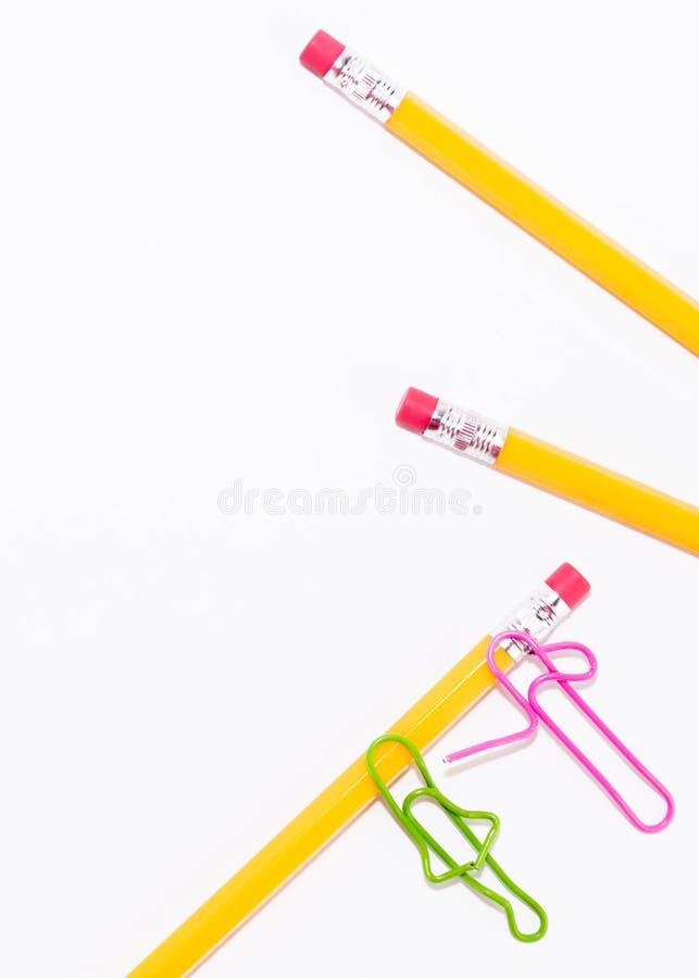 Zwei sprechende Büroklammern beim Lügen auf einem weißen Boden und auf einem Bleistift Miniaturschulleben und zurück zu Schulkonz lizenzfreies stockfoto