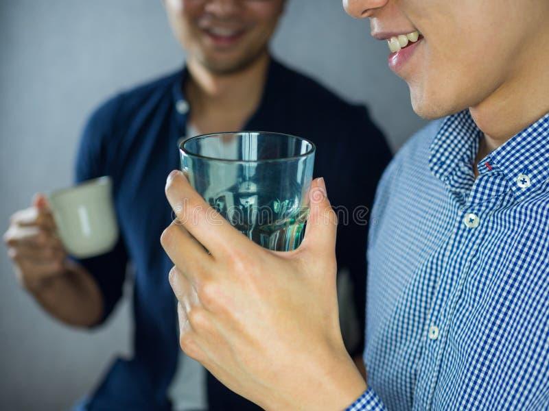 Zwei sprechende und trinkende Männer lizenzfreie stockfotos